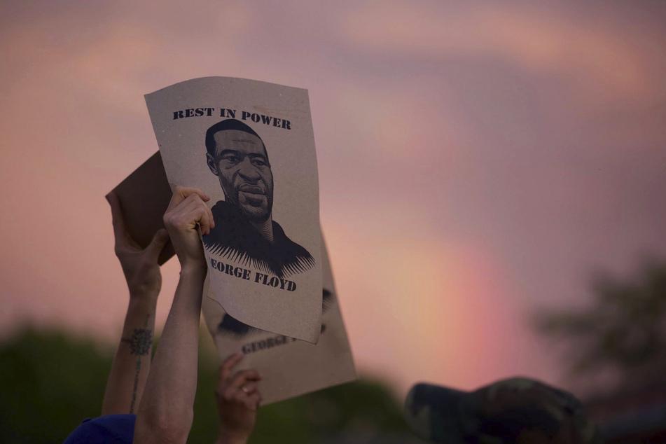 Demonstranten halten während eines Protestes Zettel mit dem Porträt von George Floyd, des in Minneapolis nach einem brutalen Polizeieinsatz gestorbenen Mannes afroamerikanischer Abstammung, in die Höhe.