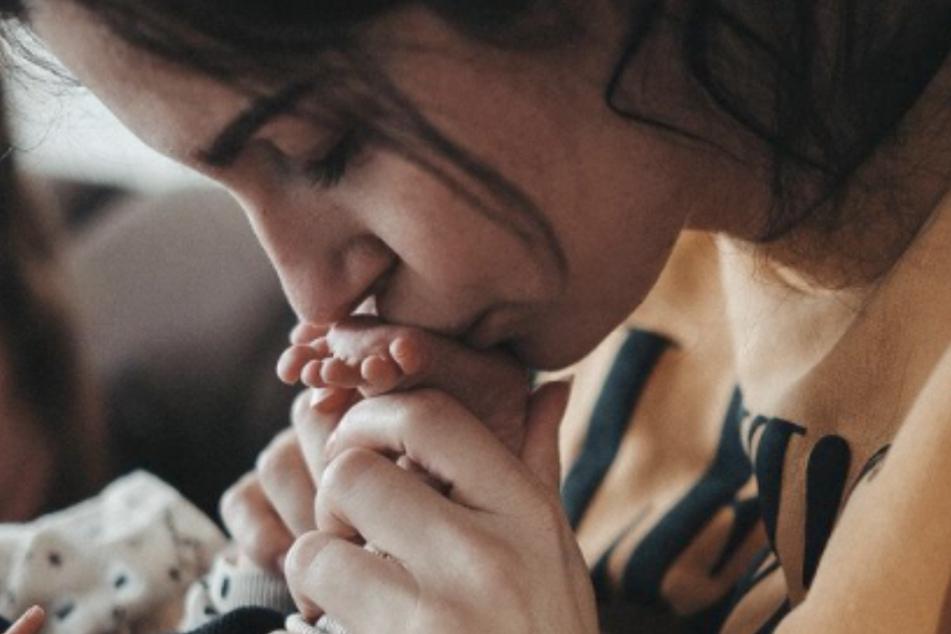 Isabel Kraus postete ein Foto auf Instagram, auf dem sie dem Neugeborenen einen Kuss auf den Fuß gibt.