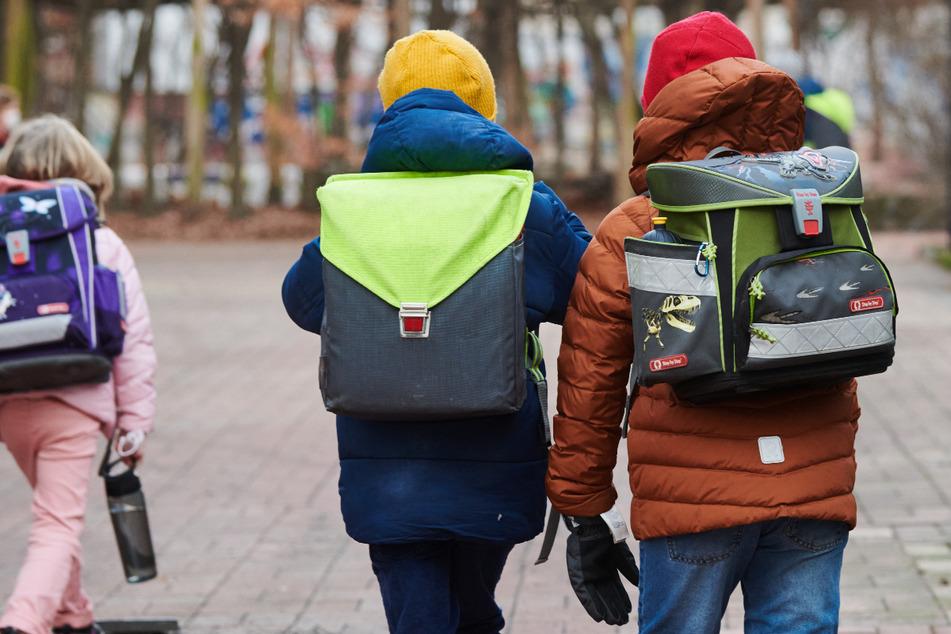 Drei Schüler gehen mit Schulranzen zum Eingang einer Grundschule in Prenzlauer Berg.