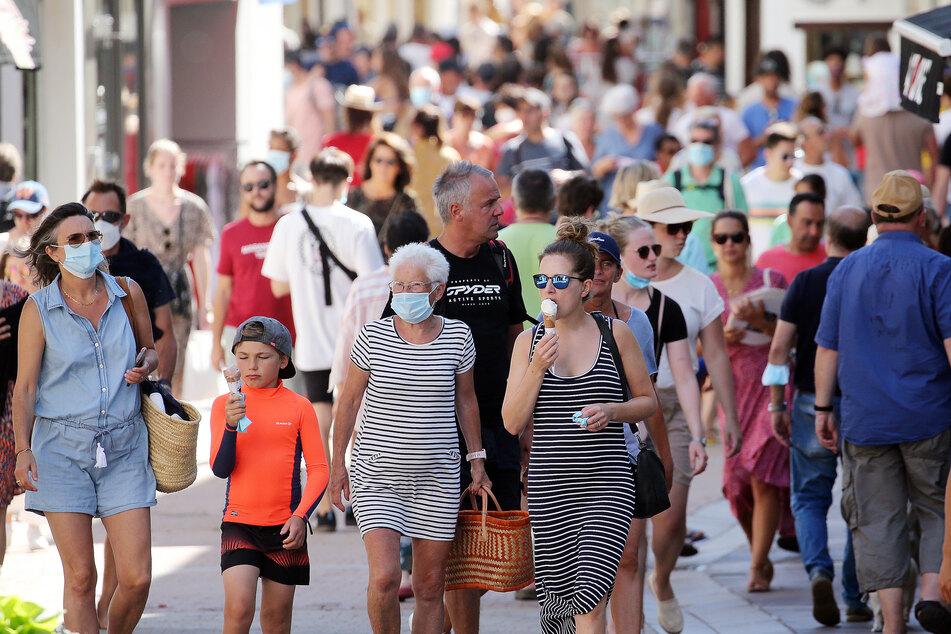 Menschen gehen durch eine Straße der Stadt. Der französische Premierminister Castex hat eine Maskenpflicht ab nächster Woche in geschlossenen öffentlichen Räumen angekündigt.