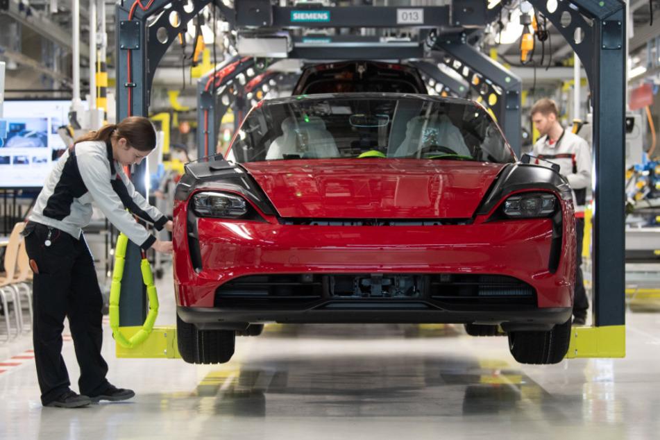 Stuttgart: Eine Mitarbeiterin der Porsche AG kontrolliert in der Produktion einen Porsche Taycan.
