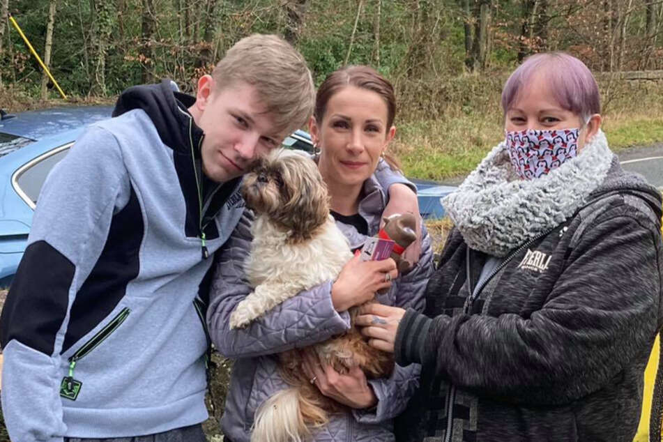 Magdalena Klubczuk (c) holds Roxy in her arms and her son nuzzles up to the old pooch.