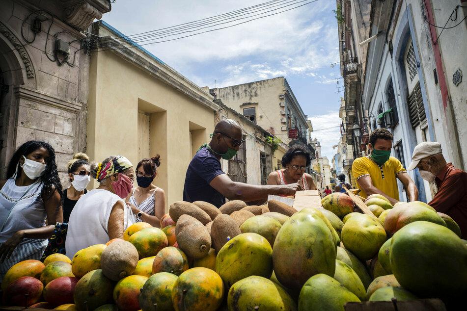Kuba, Havanna: Menschen mit Mundschutzmasken kaufen Mangos an einem Straßenstand inmitten der Corona-Pandemie. Das Tragen von Masken ist auf der Straße obligatorisch.