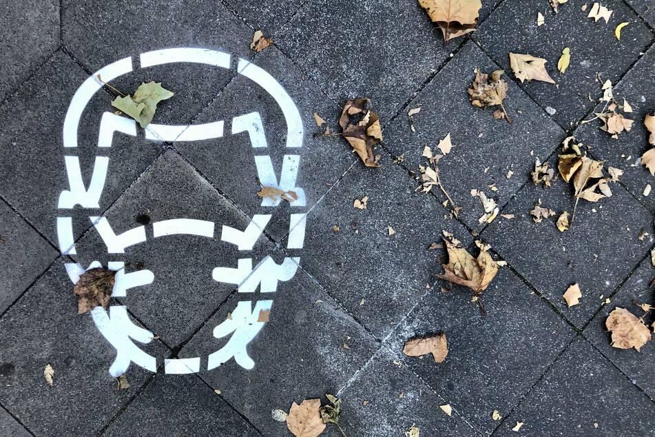 """Laut der Stadt Düsseldorf sollen an """"stark frequentierten"""" Gehwegen 600 dieser Piktogramme aufgesprüht werden, um an die Maskenpflicht zu erinnern."""