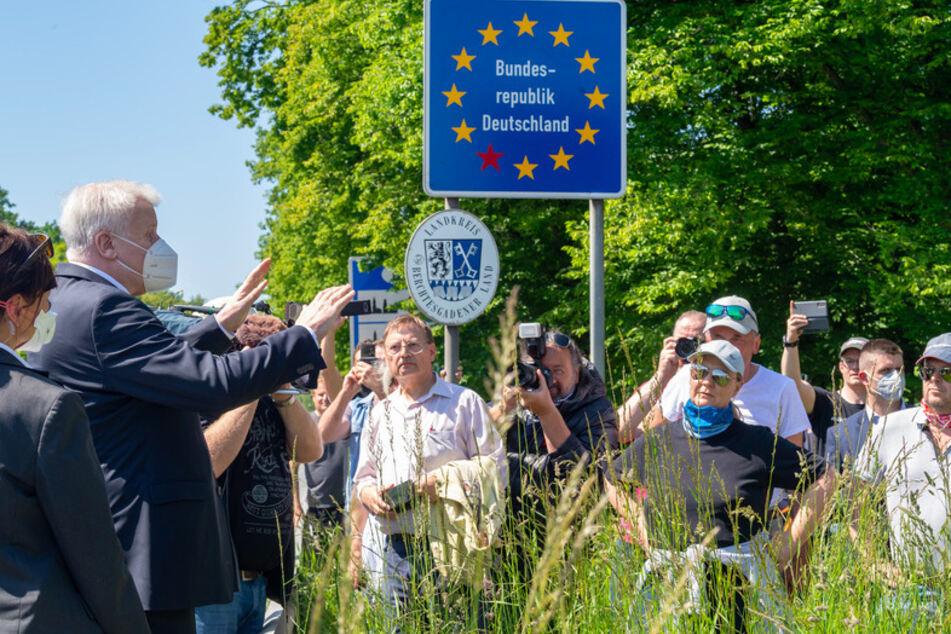 Horst Seehofer (CSU, l), Bundesinnenminister, trägt einen Mundschutz, während er sich am 18. Mai 2020 am bayerischen Grenzübergang Freilassing mit wartenden Anwohnern unterhält.