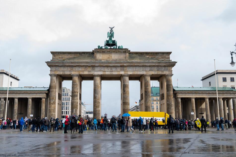 Menschen stehen bei einer Demonstration gegen die Einschränkungen durch die Pandemie-Maßnahmen der Bundesregierung vor dem Brandenburger Tor.
