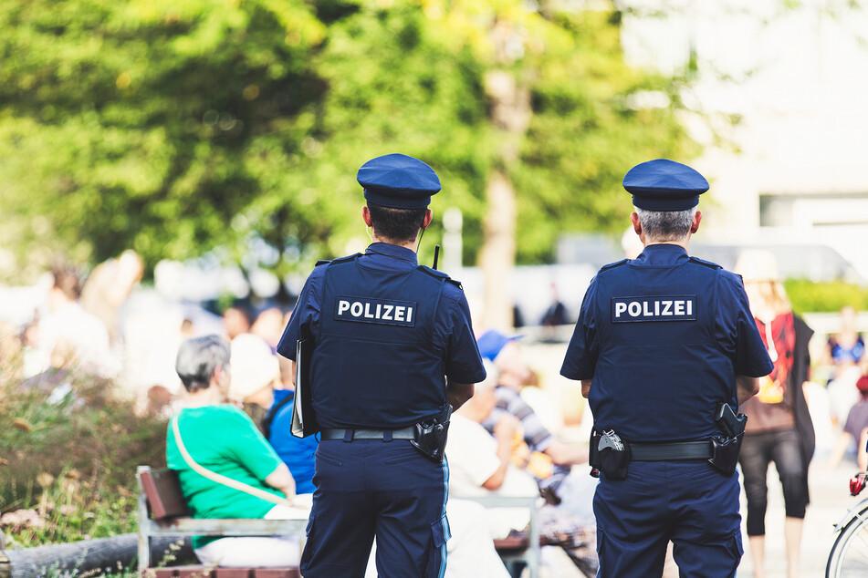 Polizisten stehen in einem Park vor einer Sitzbank. (Symbolbild)