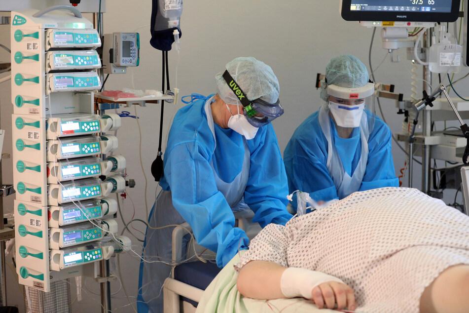 Im Infektionszimmer für Covid-19-Patienten auf der Interdisziplinären internistischen Intensivtherapiestation (ITS) der Universitätsmedizin Rostock pflegen Uta Kautz (l-r) und Nele Ehlert einen Patienten im künstlichen Koma.