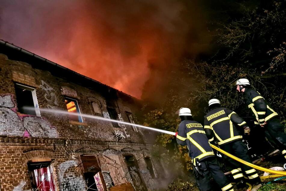 Feuerwehrleute löschen den Brand durch eines der kaputten Fenster. Das Dach steht dabei immer noch in Flammen, wie man an dem Feuerschein erkennen kann.