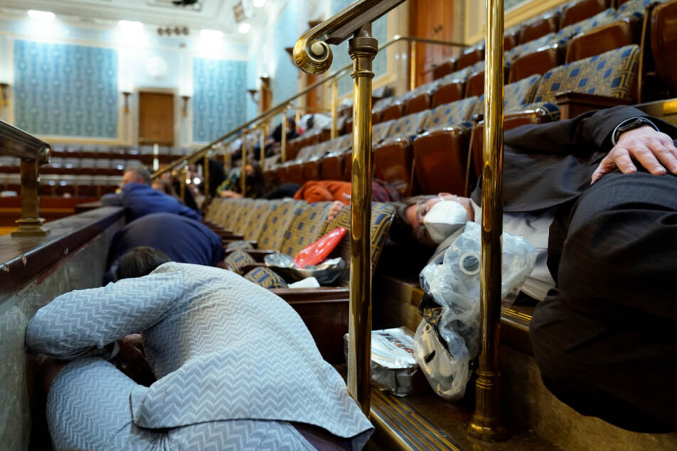 Menschen suchen Schutz auf der Tribüne des Repräsentantenhauses, während Demonstranten versuchen, in die Repräsentantenkammer im US-Kapitol einzudringen.