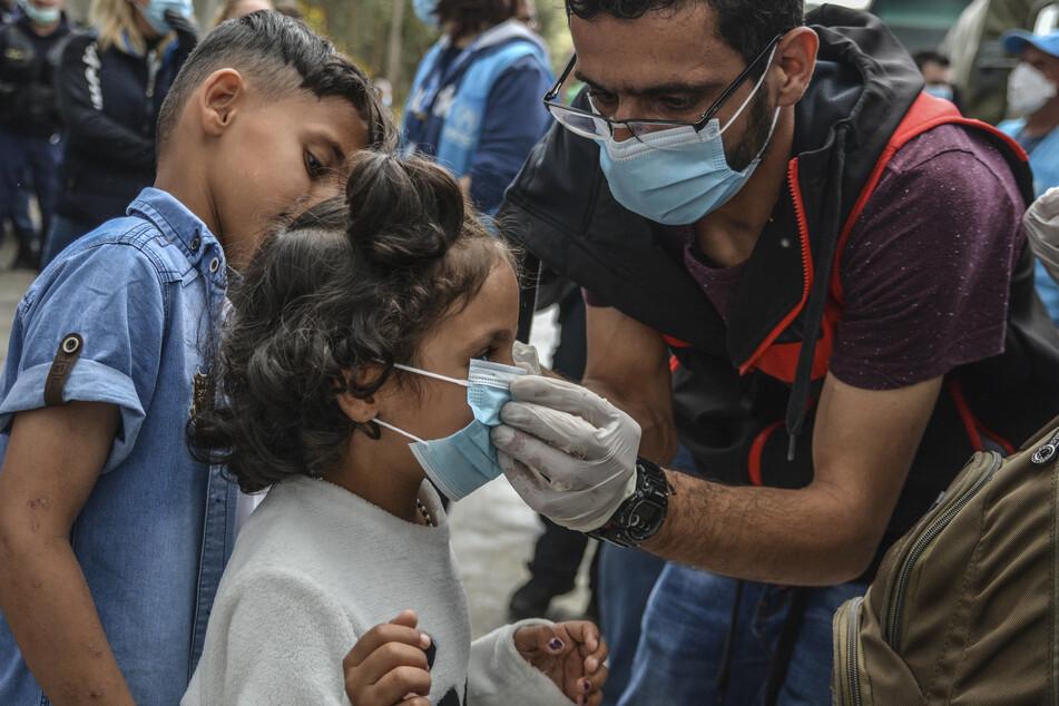 Ein Mann passt einem Kind einen Mundschutz an, während es mit anderen Migranten vor dem Lager Moria auf Busse wartet, die sie zum Hafen Mytilini bringen sollen, um anschließend mit Passagierschiffen zum Hafen von Piräus übergesetzt zu werden.