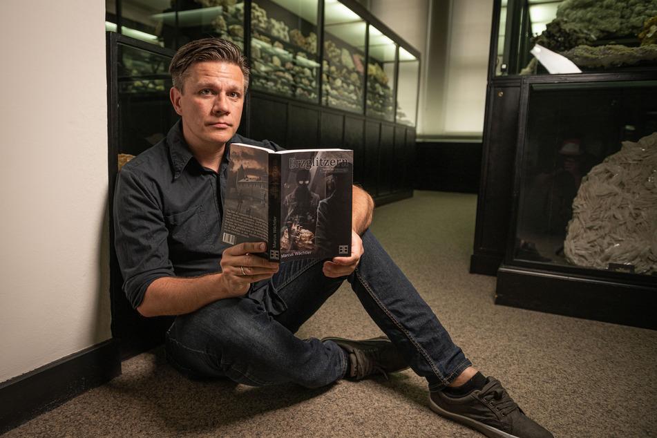 """Der Autor sitzt mit seinem Roman """"Erzglitzern"""" in der Mineralogischen Sammlung im Werner-Bau der TU."""