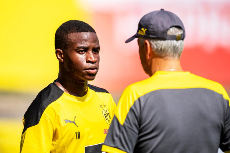 Youssoufa Moukoko (l.) lauscht BVB-Profitrainer Lucien Favre.
