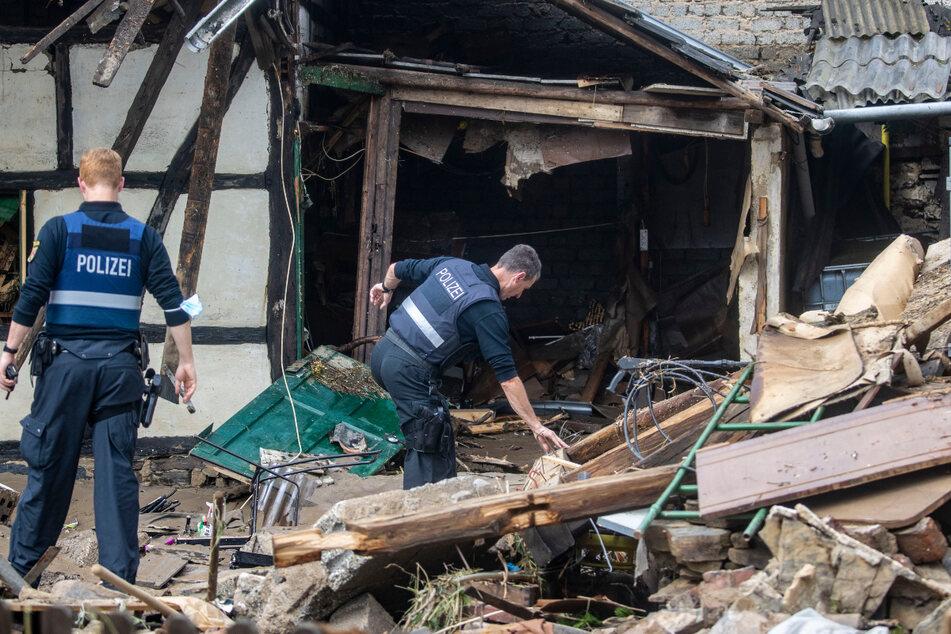 Polizisten verschaffen sich nach den Überschwemmungen in Rheinland-Pfalz einen Überblick. Mindestens sechs Häuser wurden durch die Fluten zerstört.