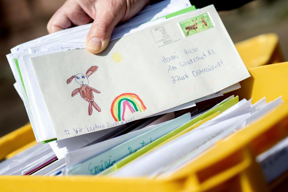 """Ein Mitarbeiter des Osterpostamts hält vor dem Gemeindehaus einen Brief in den Händen, der einen gemalten Regenbogen und die Aufschrift """"Wir bleiben Zuhause!"""" zeigt."""