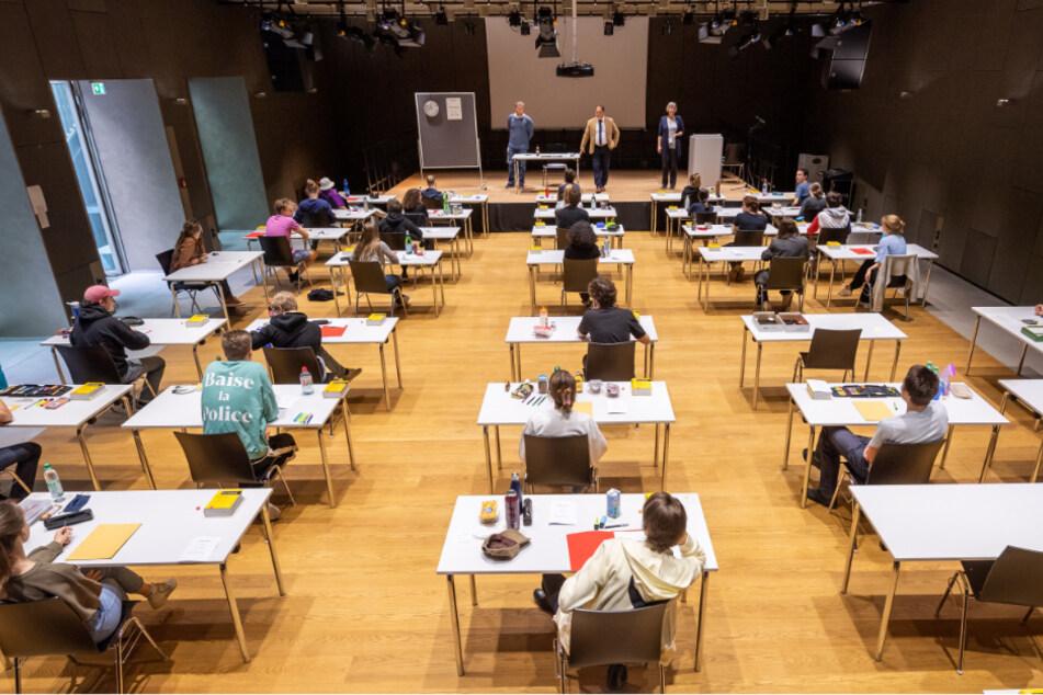 Mit weitem Abstand sitzen Schüler des Staatlichen Wilhelmsgymnasium in München zur Abiturprüfung in Deutsch an ihren Tischen in der Schulaula.