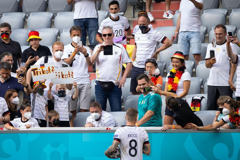 Deutschlands Toni Kroos (M.) steht nach dem Spiel bei Freunden, Familie und Fans. Nicht alle tragen eine FFP2-Maske.