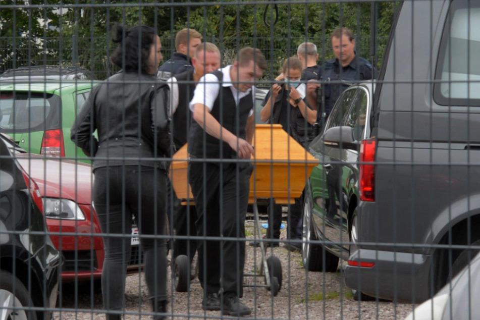 Der 29-Jährige wird in einem Sarg abtransportiert. Er wollte einen Katalysator abmontieren, dabei rutschte der Wagenheber weg und der BMW begrub den Mann.