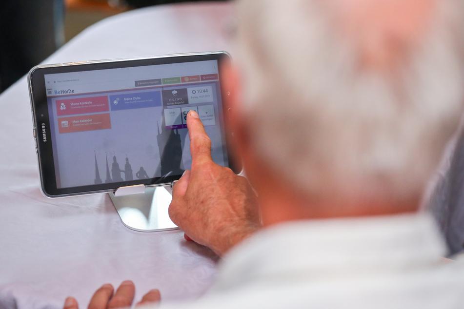 Ein Rentner spricht über einen Videoanruf via Tablet mit seinem Hausarzt.