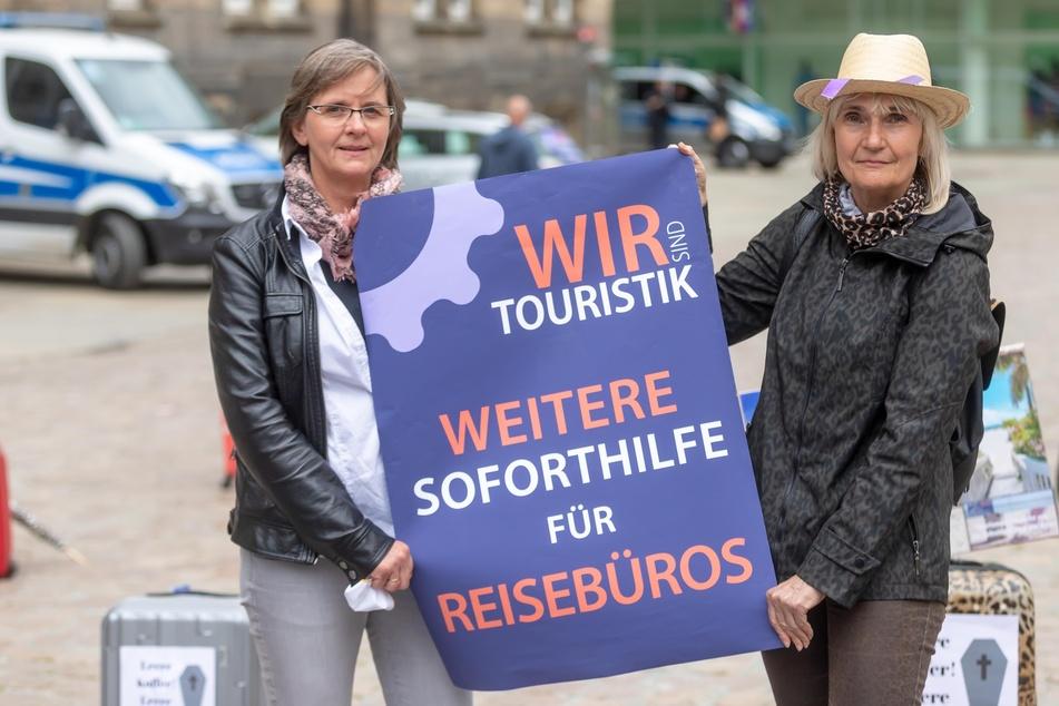 Corona-Protest vorm Chemnitzer Rathaus: Reisevermittler sitzen auf gepackten Koffern