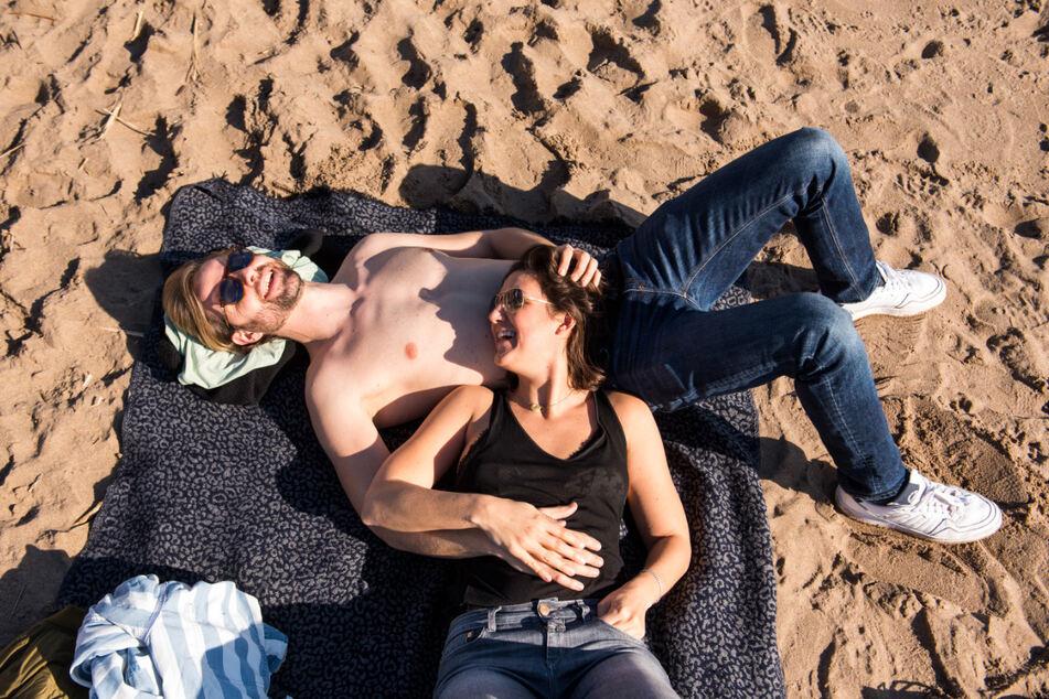 """Lasse und Tinka genießen am Strand an der Elbe in Övelgönne die Sonne. Hoch """"Ilonka"""" beschert Deutschland frühlingshaftes Wetter."""