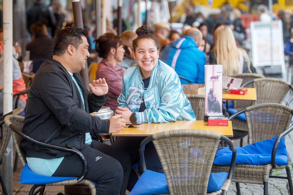 """Master Ko Chinwong (l.) und Shirley Panitz aus Berlin und Leipzig haben im Freisitz des Restaurants """"Spizz"""" Platz genommen. In Leipzig dürfen Restaurants seit dem heutigen Freitag ihre Außengastronomie öffnen."""