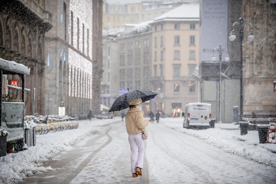 Eine Frau in Italien schützt sich mit einem Regenschirm vor Schneeflocken.