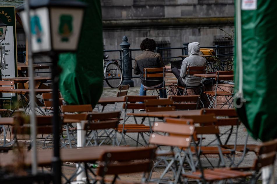 Zwei Männer sitzen auf Stühlen einer geschlossenen Außengastronomie im Nikolaiviertel.