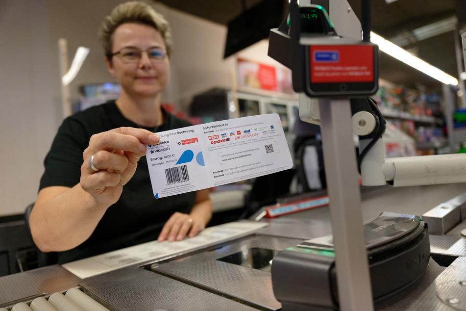 Eine Mitarbeiterin in einer Rewe-Filiale hält ein Blatt mit einem Barcode bereit. In Köln können Knöllchen seit einem Jahr auch in Geschäften bezahlt werden.