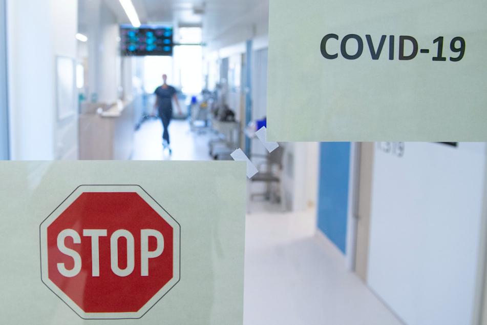 Eine Frau geht auf der Corona-Intensivstation hinter einer Glastür einen Gang entlang.