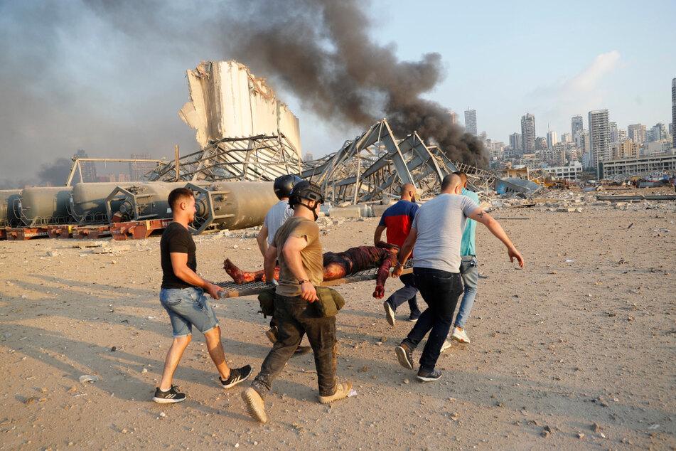 Helfer tragen ein Opfer nach der Explosion auf einer Trage, während im Hintergrund Rauch aufsteigt.