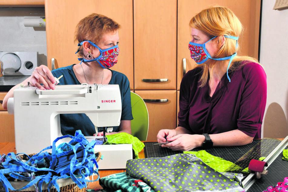 Sie wollen auch zu Hause nicht untätig sein: Anja (l.) und Katja nähen Mundschutz-Masken.