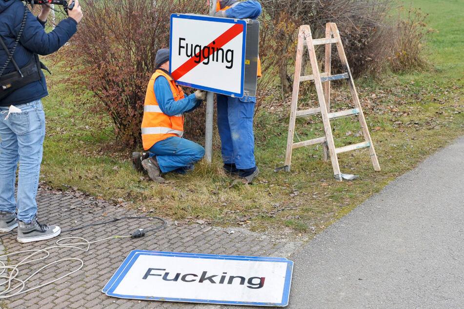 Arbeiter bringen das neue Ortschild von Fugging an.