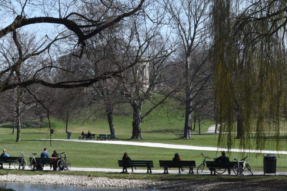 Mehrere Menschen sitzen auf Bänken vor dem Monopteros im Englischen Garten.