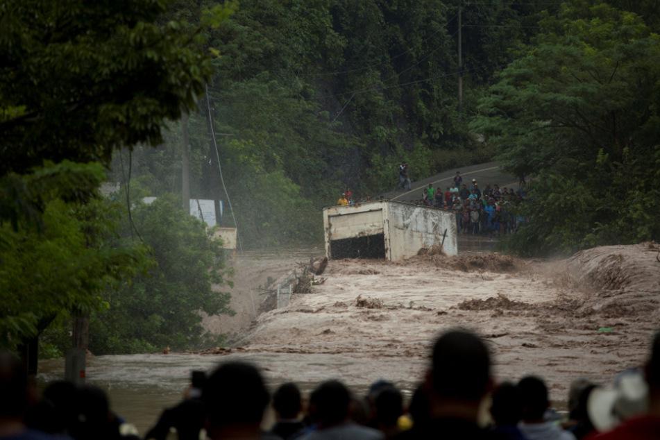 """Guatemala, Camotan: Dorfbewohner schauen zu, wie ein Lkw vom Strom des Rio-Grande-Flusses nach dem Durchzug von """"Iota"""" gezogen wird."""