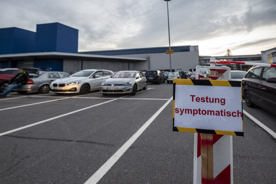 Im roten Warte-Bereich vor der Messe parken Autos dicht an dicht und mit offenen Fenstern. Fußgänger müssen frieren.