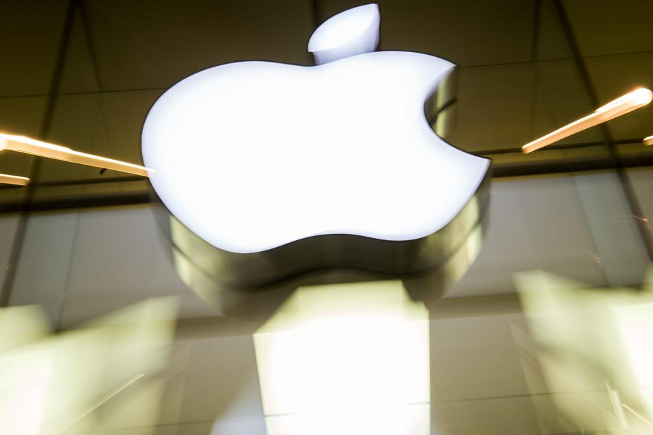 Das Apple-Logo leuchtet an der Fassade des Apple-Store in München.