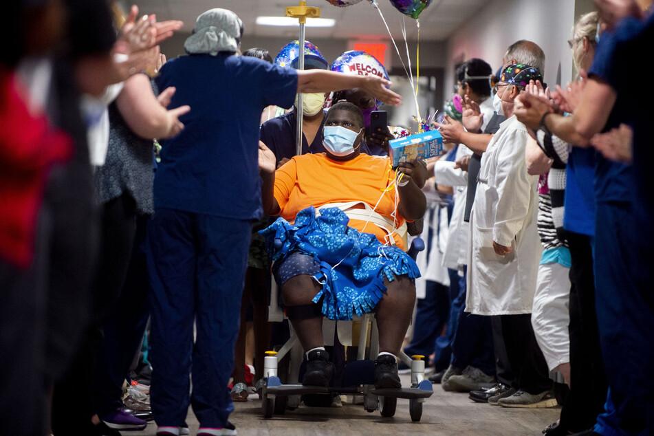 Krankenpfleger und Ärzte säumen den Saal, während Terrell Harris nach einem 15-wöchigen Kampf gegen Covid-19 das Krankenhaus verlässt. Harris wurde am 28. März ins Krankenhaus eingeliefert, als er positiv auf auf das Coronavirus getestet wurde.