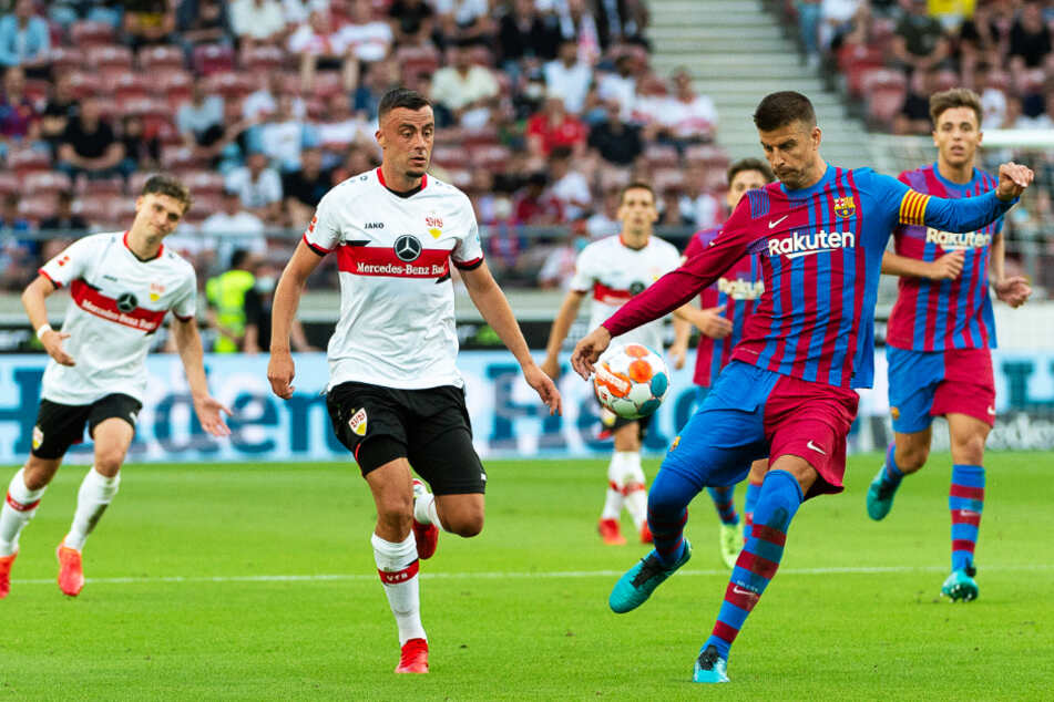Barcelonas Kapitän Gerard Piqué (r.) klärt den Ball vor Stuttgarts Philipp Förster.