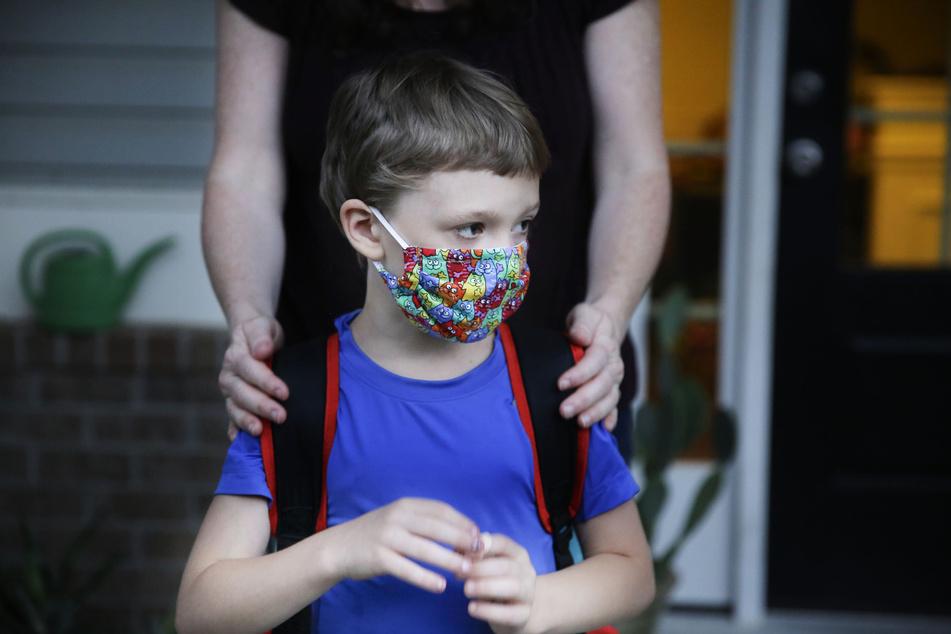 Ein Junge steht mit einem Mundschutz auf einer Veranda. (Symbolbild)