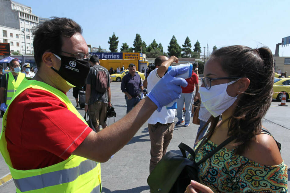 A medical employee wearing a protective mask measures the body temperature of passengers on a ferry at the port.