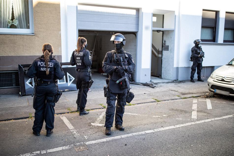 Wuppertal: Polizeibeamte stehen vor einem Wohnhaus. Bei einer Razzia gegen Clankriminalität sind in Nordrhein-Westfalen am frühen Morgen mehrere Wohnungen und Firmen durchsucht worden.