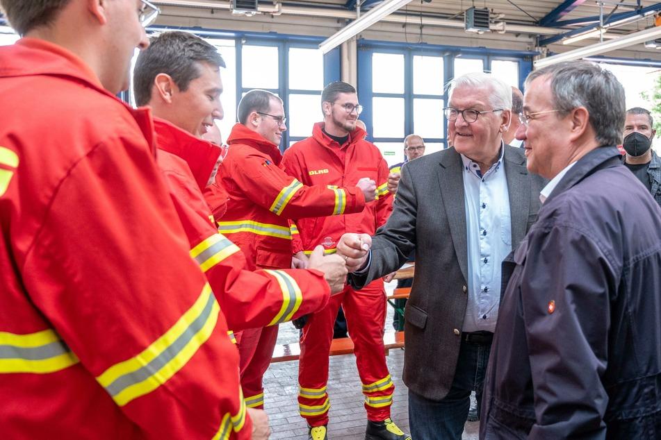 Nordrhein-Westfalen, Erftstadt: Bundespräsident Frank-Walter Steinmeier (2. v.r.) und Armin Laschet (r, CDU), Ministerpräsident von Nordrhein-Westfalen, unterhalten sich bei einem Besuch der Feuerwehrleitzentrale mit Helfern der Deutschen Lebens-Rettungs-Gesellschaft (DLRG).