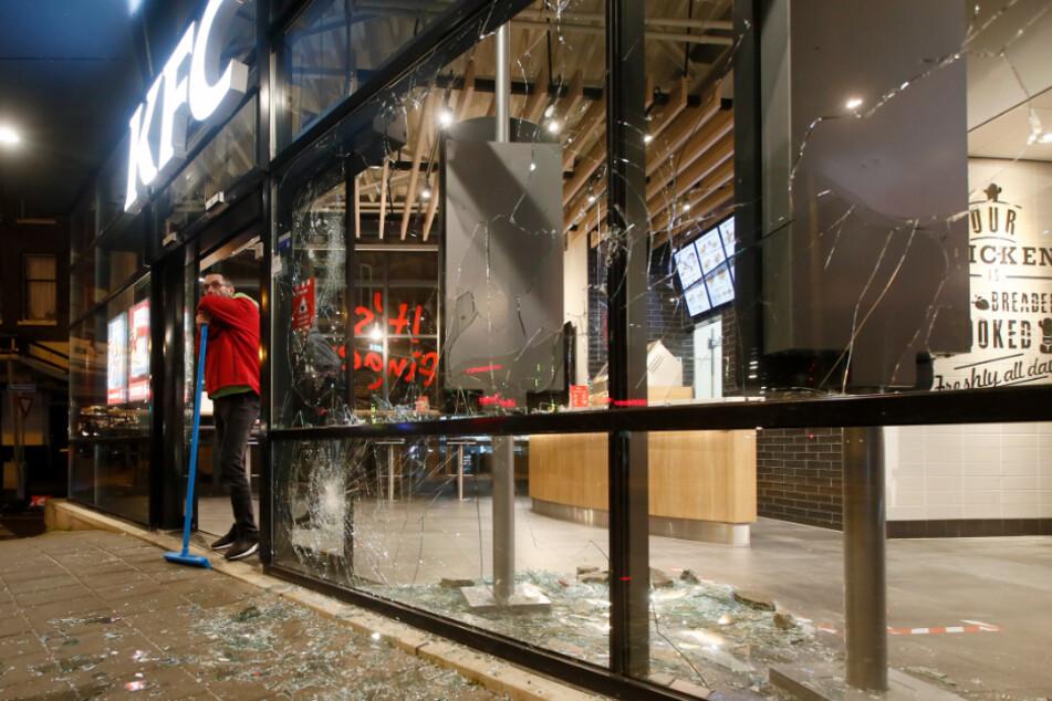 Ein Mann ruht sich auf seinem Besen aus, während er neben Glasscherben und zertrümmerten Fenstern eines Fast-Food-Restaurants steht.