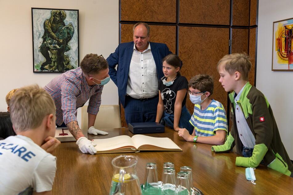 Gemeinsam mit OB Hilbert (49, FDP, M.) und Protokollar Stefan Börner (33) durften die Kinder im Goldenen Buch blättern.