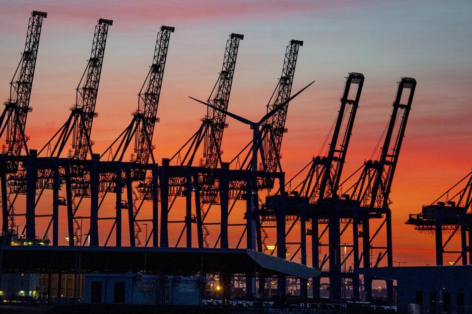 Die Sonne geht hinter den hochgeklappten Containerbrückenkränen, die normalerweise Schiffe entladen, im Hamburger Hafen unter. (Symbolfoto)