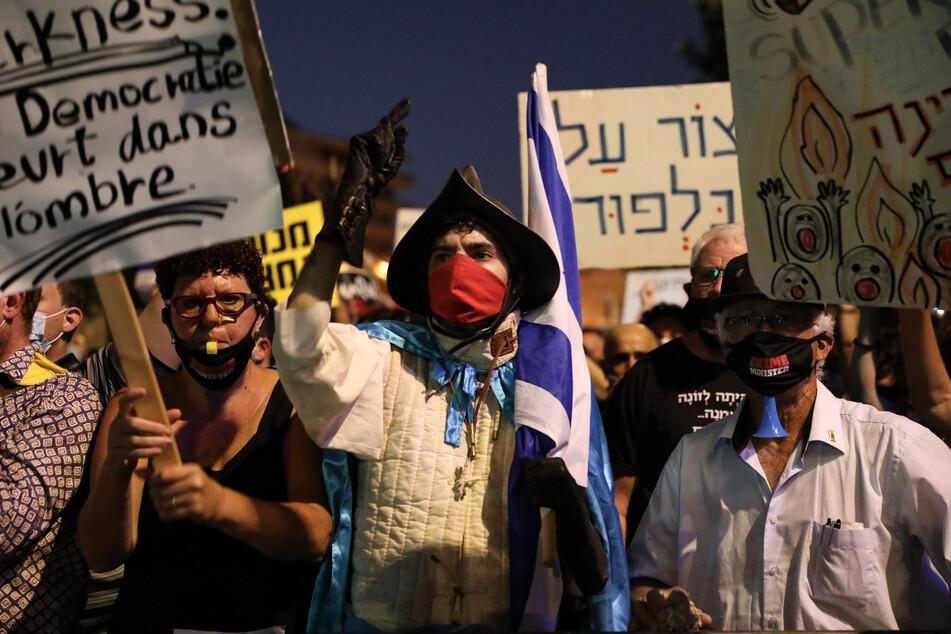 Demonstranten halten Plakate und Fahnen bei einem Protest gegen den israelischen Premierminister Netanjahu in der Nähe seiner Residenz in die Höhe.