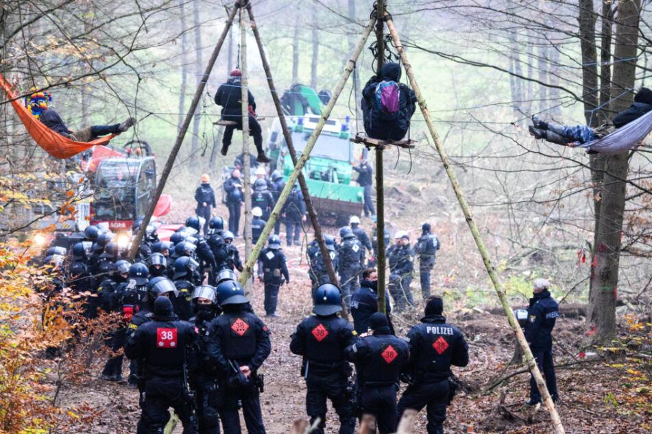 Einsatzkräfte der Polizei stehen bei Baumbesetzern im Dannenröder Forst, die in Tripods und Hängematten verharren.