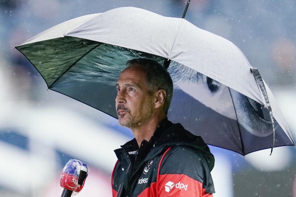 Frankfurts Trainer Adi Hütter kommt mit Regenschirm ins Stadion. (Symbolfoto)