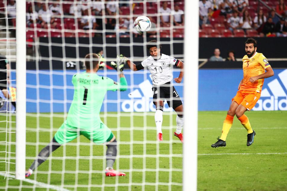 Die frühe Führung: Serge Gnabry (M.) jagt die Kugel an Armeniens Keeper David Yurchenko (l.) vorbei zum 1:0 ins Netz.